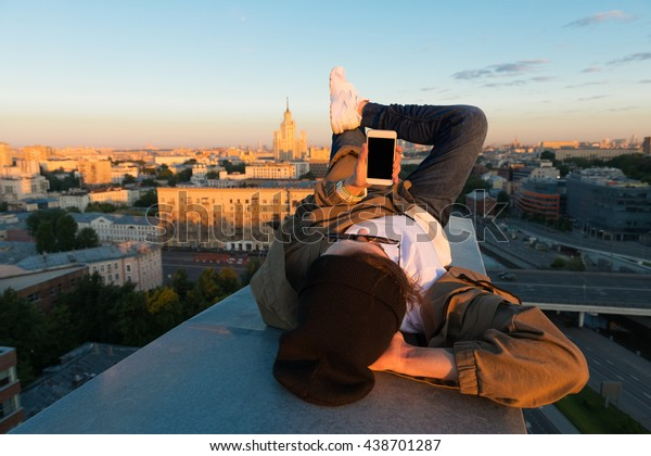 MOSCOW, RUSSIA - JUNE 13, 2016: Young and brave male sitting on the edge of high roof looking at phone similar to iphone and stunning view of city in the summer during dawn