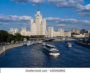 Moscow, Russia - June 16, 2019: Stalin skyscraper on Kotelnicheskaya Embankment and in front of it is a river along which the tourist motor ship icebreaker River Palace by Radisson Royal Flotilla