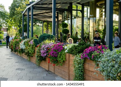 Moscow, Russia - June 16, 2019: Open cafe with beautiful flowers  in Zaryadye Park. Zaryadye is new tourist attraction of Moscow near the Kremlin. Many people come here to relax with their families