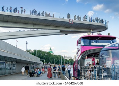 Moscow, Russia - June 16, 2019: Floating bridge in Zaryadye Park above Moskva River. Zaryadye is new tourist attraction of Moscow near the Kremlin. Landing on  pleasure boat on Moskva River