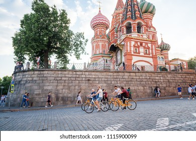 Moscow, Russia. June, 18, 2018. Tourists ride bicycles along Red Square overlooking the Cathedral of St. Basil the Blessed