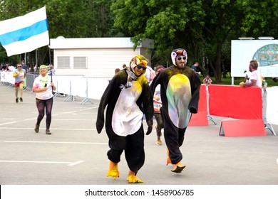 Moscow, Russia, June 2, 2019: Two young men in funny penguin costumes at the festival of colors. Holi festival.