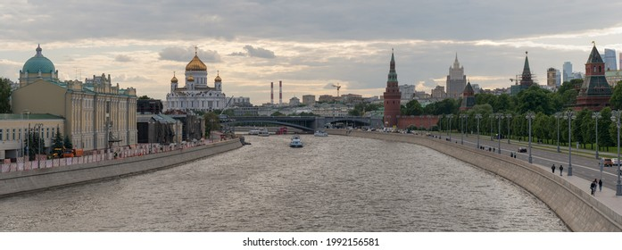 Moscow, Russia - June 2 2021: Moscow cityscape in the summer day. Red Kremlin Towers, Cathedral of Christ the Saviour, Moskva River, traffic at the embankment, walking people. Panoramic photography