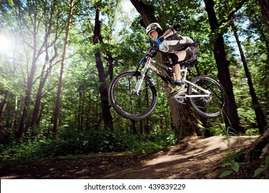 MOSCOW, RUSSIA - JUNE 20, 2016: Rider in action at mountain bike sport. Jump on a mountain bike. Biker making a stunt and jumps in the forest. Cool athlete cyclist on a bike. MTB biking.