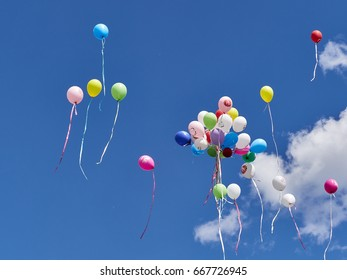 Moscow. Russia, June 2017, a bunch of multi-colored balloons with congratulations flies into the sky with clouds on a summer sunny day