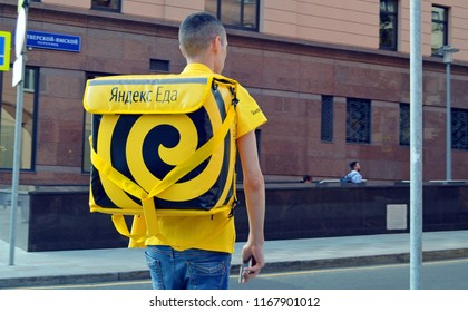 """MOSCOW, RUSSIA - JUNE, 2018: Courier service fast delivery of food """"Yandex Food"""" on the street in the center of Moscow"""