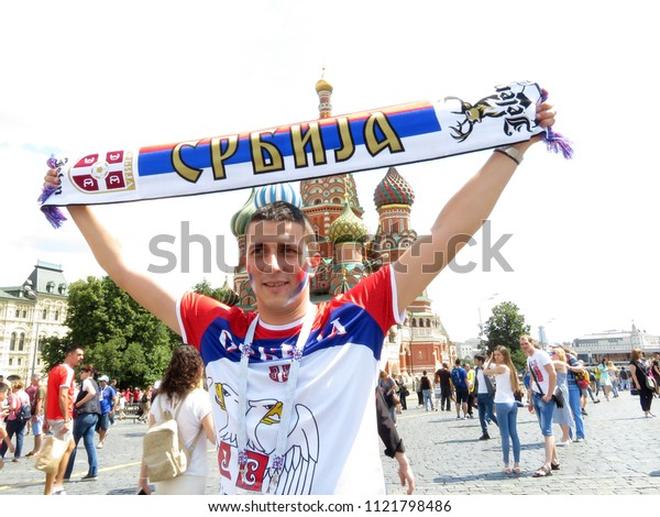 Moscow, Russia - June 2018: Football fan from Serbia on Red Square in Moscow during the FIFA 2018 World Cup. Happy serbian guy cheering for national team