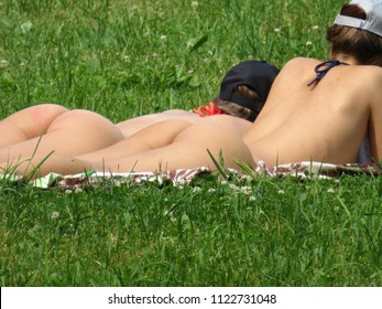 Moscow, Russia - June 2018: Young women nudist sunbathing on a green grass, rear view. Naked girls, nudist beach, sexy slim buttocks