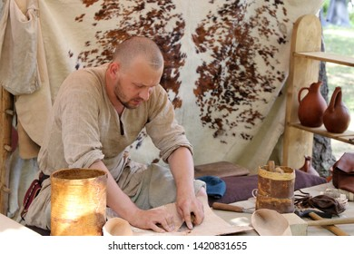 Moscow, Russia - June 2019: Craftsman in medieval clothes treats the bark of a tree and leather during the Moscow historical festival Times and epochs. Artisan in Europe of middle ages