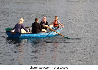 Moscow, Russia - June 2019: Family rides in rowing boat on a lake in Izmailovo park. Parents with children having fun, leisure on a water