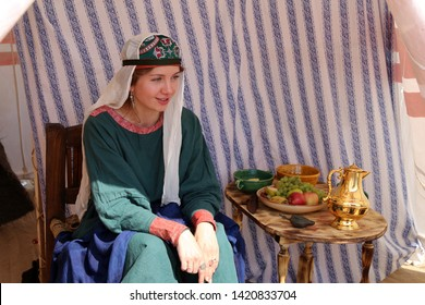 Moscow, Russia - June 2019: Noble woman in Byzantine clothes sitting near the table with dishes during the Moscow historical festival Times and epochs. Reconstruction of life in the Byzantine Empire