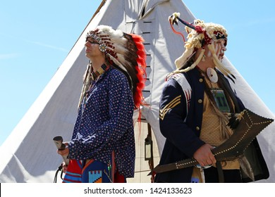 Moscow, Russia - June 2019: North American Indians stand with weapon near a wigwam against the blue sky. Reconstruction of native american life on Moscow historical festival Times and epochs