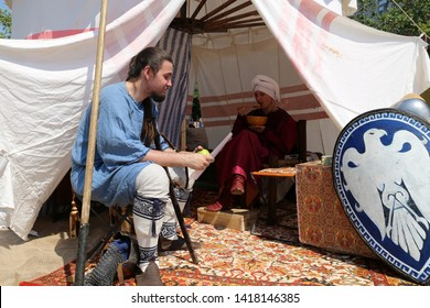 Moscow, Russia - June 2019: People in Byzantine clothes of 10th century in a aristocrat's tent during the Moscow historical festival Times and epochs. Reconstruction of life in the Byzantine Empire