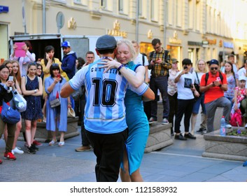 MOSCOW, RUSSIA - JUNE 22: Fan of Argentina dancing with young woman in the street of Moscow on June 22, 2018.