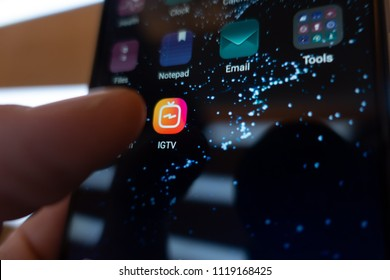 Moscow, Russia - June 23, 2018: Instagram IGTV. Man hand presses the button phone IGTV. Icon IGTV Closeup. Editorial.