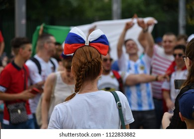 Moscow, Russia - June 23, 2018: Russian girl football fan looks on the fans from abroad on the Nikolskaya street. World Cup 2018. FIFA world cup, Mundial 2018.