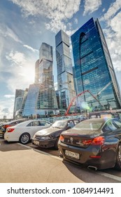 Moscow, Russia - June 24, 2017: Cars parked on a street near Moscow city skyscrapers under a blue cloudy sky