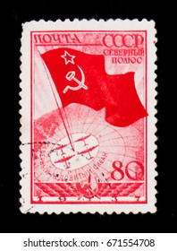 MOSCOW, RUSSIA - JUNE 26, 2017: Rare stamp printed in USSR (Russia) shows Flag with star, and polar planes on globe, circa 1937