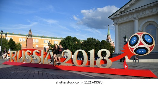 Moscow, Russia - June 26, 2018: football fans sit on the Welcome billboard World Cup 2018 on Manege Square in Moscow. FIFA world cup, Mundial 2018