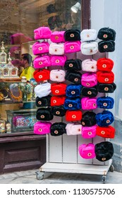 MOSCOW, RUSSIA - June 26, 2018: Souvenir hats with ear flaps of different colors with Soviet cockades on the street stand in front of a souvenir shop window on Nikolskaya street