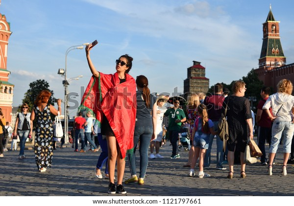 Moscow, Russia - June 26, 2018: Moroccan football fan girl takes selfie on the background of the Kremlin on the Red Square in Moscow. FIFA world cup, Mundial 2018