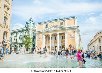 MOSCOW, RUSSIA - June 29, 2018: Birzhevaya square. The Chamber of Commerce and Industry of the Russian Federation. People splash in the fountain in hot weather