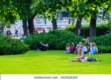 Moscow, Russia - June, 3, 2019: image of boys and girls sitting on the lawn in the Alexander Garden in Moscow