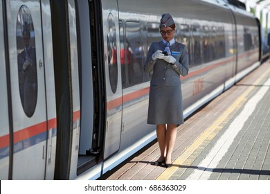 MOSCOW, RUSSIA - JUNE 30, 2017. The train conductor waiting for the passengers of the high speed electric train Sapsan between Moscow and Saint Petersburg. Moscow, Russia