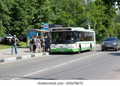 Moscow, Russia - June 4, 2016: Green public bus LIAZ on stop at the city street. People on station are going to enter into public vehicle on summer day.