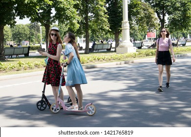 Moscow, RUSSIA - June 5, 2019 two sisters on scooters are talking