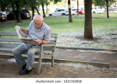 Moscow, RUSSIA - June 5, 2019 An elderly gray-haired man carefully reads a newspaper while sitting on a bench in the park.