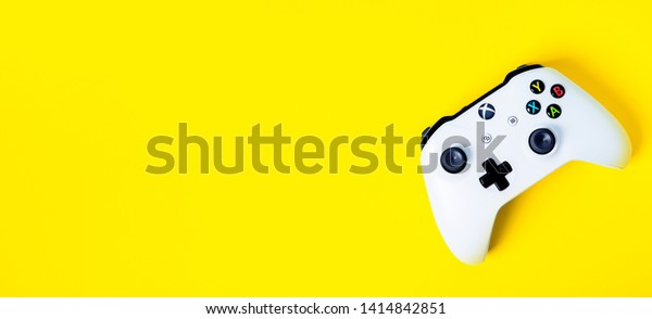 Moscow, Russia - Juney 03 2019: white Wireless Gamepad Xbox One S controller joystick on yellow background with copy space. Creative Minimal Gaming concept.