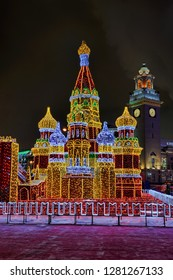 "MOSCOW, RUSSIA - Light Decoration ""St. Basil's Cathedral ""  illuminated with hundreds of LED lights at Kievskaya metro station with a clock tower of Kievsky Railway Station in the background at night."