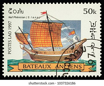 """Moscow, Russia - March 03, 2018: A stamp printed in Laos shows ancient Phoenician ship, series """"Sailing Ships"""", circa 1997"""