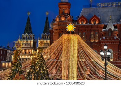 MOSCOW, RUSSIA - March 03, 2019 Twilight view of illuminated colorful tent topped with sun at Manezhnaya Square in twilight during Russian holiday Maslenitsa. The State Historcal Museum in background.