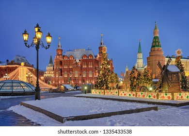 MOSCOW, RUSSIA - March 03, 2019 Twilight view of the beautiful decorations on Manezhnaya square with illuminated tent and fir trees topped with a sun. State Historcal Museum in the background.