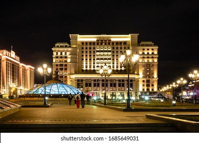 MOSCOW, RUSSIA - MARCH 12, 2020: people walk on Manezhnaya Square near Hotel Moskva (Four Seasons) in Moscow city at night. Manege Square is pedestrian open space in center of Moscow city
