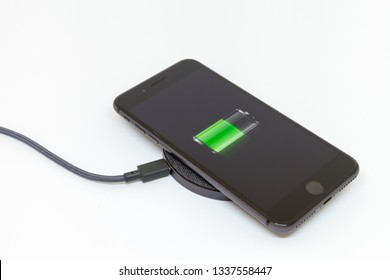 Moscow / Russia - March 13, 2019: A black iPhone lies on a wireless charger. On-screen icon for half charged battery