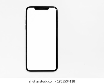 Moscow Russia March 14, 2021 .iPhone11 Pro Max, modern mobile phone with blank white screen isolated on white background.  Top view, close-up, flat lay, copy space.