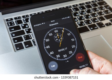Moscow / Russia - March 15, 2019: Black iPhone in hand on the background of the MacBook. Stopwatch on screen