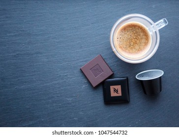 MOSCOW, RUSSIA - MARCH 16, 2018: Nespresso Dark Chocolate Squares and Coffee Capsule and Cup of Coffee on Grey Black Background Top View Natural Light Selective Focus