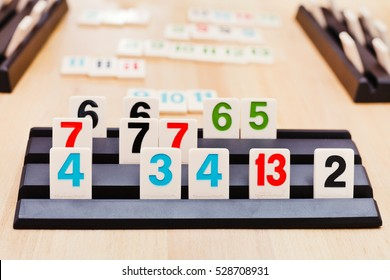MOSCOW, RUSSIA - MARCH 17, 2014: tile sets in playing rack of Rummikub board game. Rummikub was invented by Ephraim Hertzano in the early 1930s.