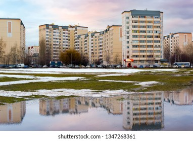 MOSCOW, RUSSIA - MARCH 2019: South Butovo district. Urban houses and sky with clouds reflected in puddle from melting snow on street in sunny spring day