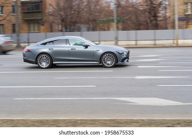 Moscow, Russia - March 2021: side view of gray Mercedes-AMG GT 4-Door Coupe. Fast moving car on the street. Vehicle driving along the street in city with blurred background.