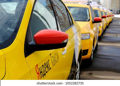 MOSCOW, RUSSIA - March 22 2018:Taxi sign and Yandex taxi write on board on the yellow new cars