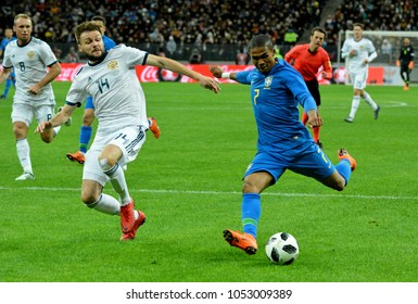 Moscow, Russia - March 23, 2018. Russian centre-back Vladimir Granat and Brazilian winger Douglas Costa during international test match Russia vs Brazil in Moscow.