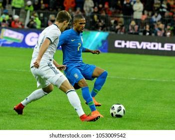 Moscow, Russia - March 23, 2018. Russian midfielder Roman Zobnin and Brazilian winger Douglas Costa during international friendly match Russia vs Brazil in Moscow.