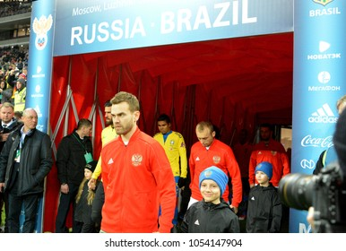 Moscow, Russia - March 23, 2018. Russian team captain and goalkeeper Igor Akinfeev coming on pitch, followed by Denis Glushakov,  for international test match against Brazil.
