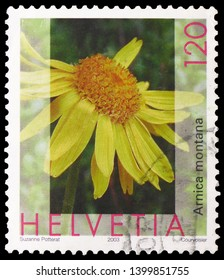 MOSCOW, RUSSIA - MARCH 23, 2019: Postage stamp printed in Switzerland shows Arnica, Leopard's Bane (Arnica montana), Flora serie, circa 2003