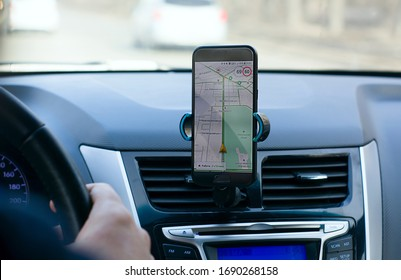 Moscow, Russia, March 23, 2020: the driver's hand on the steering wheel of the car on the dashboard map of the city on the Navigator view from the back seat